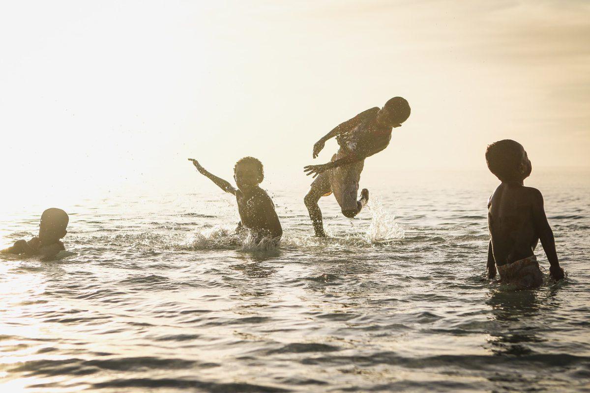 Children splash around in clean water with white sunlight shining on them.