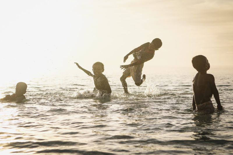 Children splash around in clean water with white sunlight shining on them.